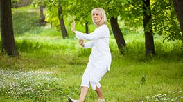 Woman in the park doing tai chi