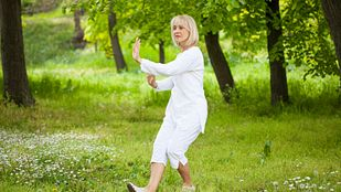 Woman int he park doing tai chi