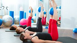 women lying on exercise mat with Pilates ball
