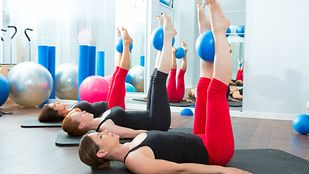 woman lying on exercise mat with Pilates ball