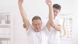 Man performing overhead shoulder exercise with physical therapist.