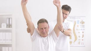 older man performing exercise with physical therapist
