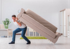 Image of man lifting a couch on his back