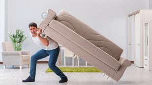 Man lifting a couch on his back