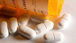Prescription bottle and pills spilled on table