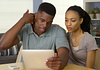 Image of young man with neck pain looking up information on an ipad with his partner