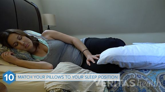 Woman sleeping on her side with pillow between her knees.