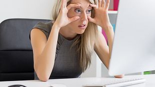 Woman trying to stay awake at her computer