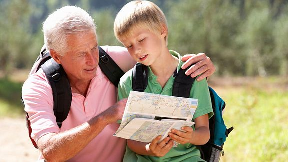 A grandpa bending down to show his grandson a map