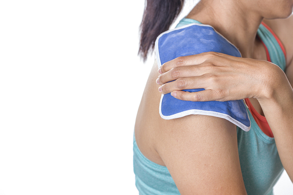 woman using heating pad on shoulder
