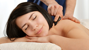 Image of woman getting gua sha treatment on her neck