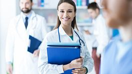 Medical professionals standing holding clipboards
