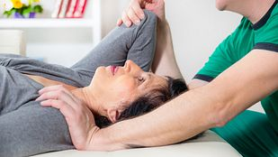 Therapist assisting patient with shoulder stretch.