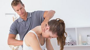 Male physical therapist examining a young woman's cervical and thoracic spine in the medical office