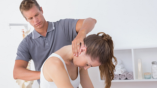 image of a male physical therapist examining a young woman's cervical and thoracic spine in the medical office