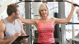 Woman doing arm exercises with a trainer in a gym.