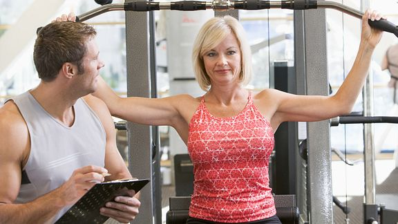 A personal trainer working with a woman at a gym who is using a workout machine