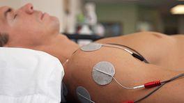 Electotherapy unit attached to a patient's shoulder.