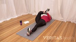 Woman laying on her back with her knee bent at a 90 degree angle while holding her ankle to stretch the piriformis muscle