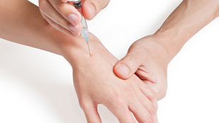 image of needle being injected into a hand.