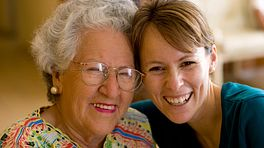 Elderly woman and a younger woman smiling