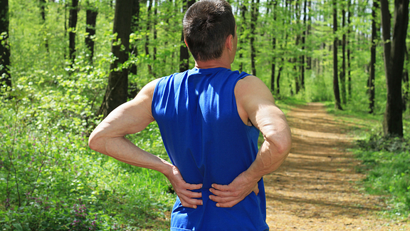 Image of runner in the woods with back pain