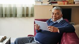 Man recovering at home while on his tablet.