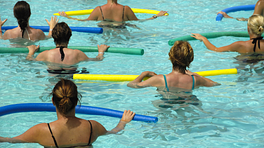 Group performing water aerobics in a pool