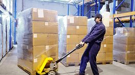 Using a hand truck in a warehouse.