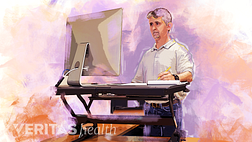 Illustration of a man using a standing desk converter in his office