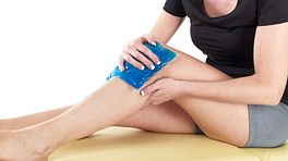 Woman sitting down with an icepack on her knee.