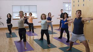 Yoga class doing warrior 2 yoga pose