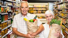 Elderly couple holding grocery bags full of produce in a grocery store aisle