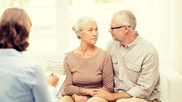 Elderly couple talking with a physician.