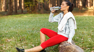 Image of woman sitting on a log in the forest drinking water