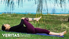 Woman lying on her back outdoors doing a supine piriformis stretch