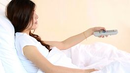 Woman sitting up in bed, watching television.