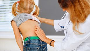 Doctor examining young patient's spine