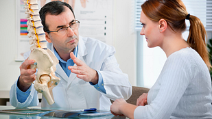 Doctor and patient having a discussion in an office while looking at a model skeleton.