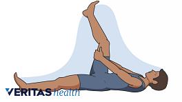 Man lying on back doing hamstring stretch.