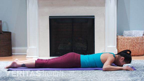 Woman laying face-down on a mat performing the prone cobra neck strengthening exercise