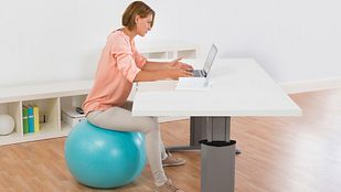 Woman sitting on an exercise ball at her desk.