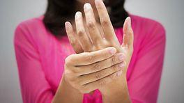 Woman wearing a pink shirt, grabbing her hands in pain.