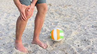 Closeup image of person grabbing knee on with volleyball in the sand next to them