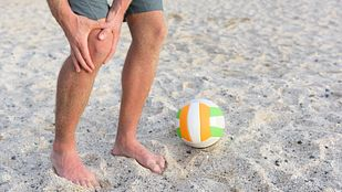 Beach volleyball player grabbing knee in pain.