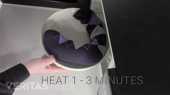 Putting a sock heat pack into the microwave.