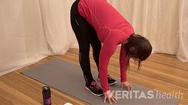 Woman bent at the waist and touching the floor with her fingertips to stretch her hamstring muscles