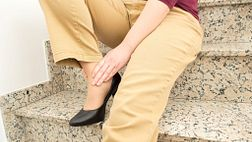 Woman wearing high heels holding her ankle in pain.
