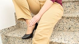 Closeup image on woman in heels on stairs holding her ankle