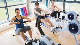 Rowing machines in use at the gym
